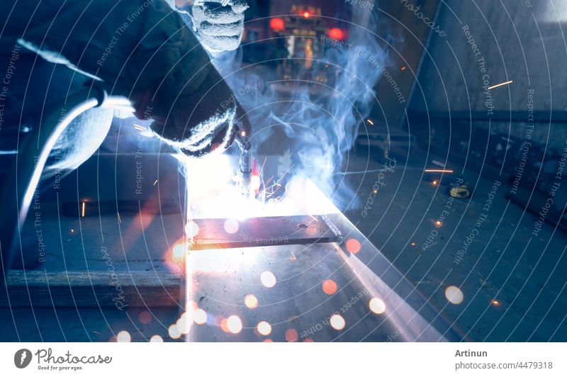 Welder welding metal with argon arc welding machine and has welding sparks and smoke. Man wear protective gloves. Safety in industrial workplace. Welder working with safety. Steel industry technology.