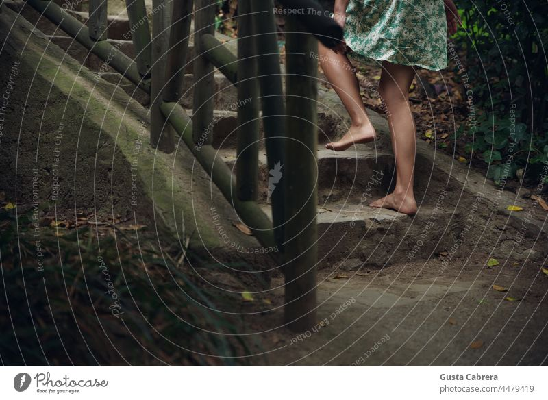 Bare feet climb stone stairs and wooden railing. Barefoot ladders Walking Exterior shot Colour photo conceptual Feet