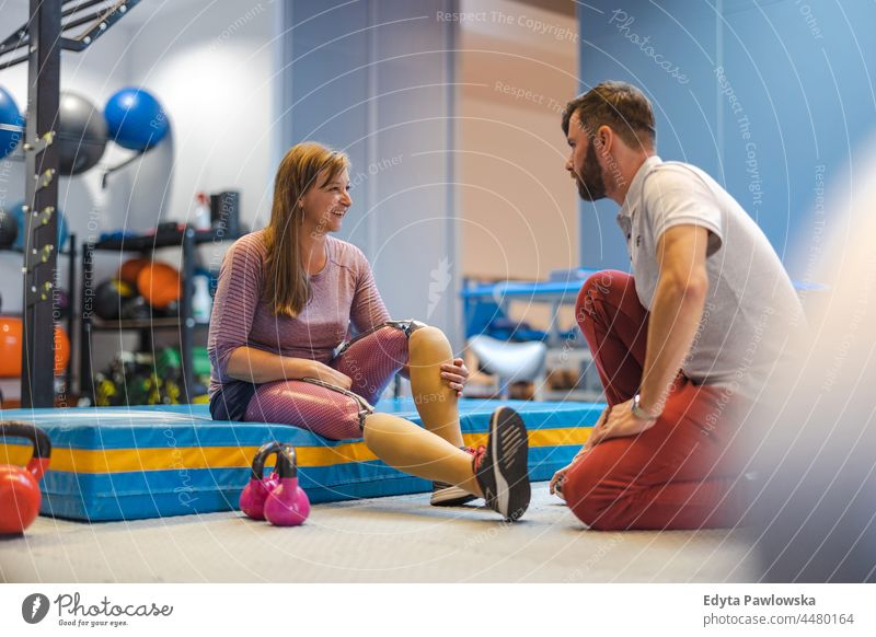 Woman with prosthetic legs talking to a physiotherapist physiotherapy determination recovery rehabilitation strength workout exercise fitness training woman