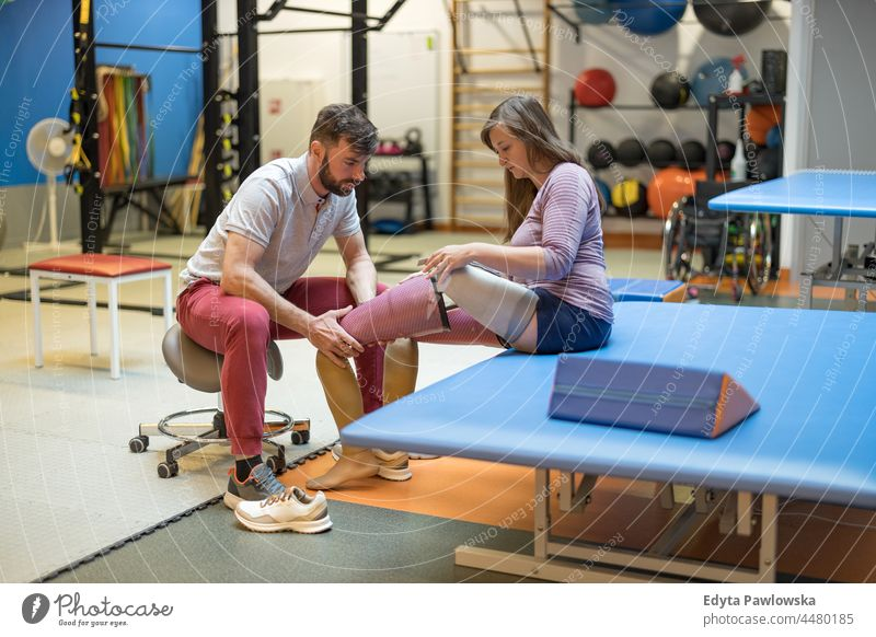 Physiotherapist helping young woman with prosthetic legs physiotherapy determination recovery rehabilitation strength workout exercise fitness training sport