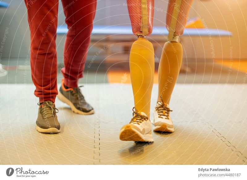 Close-up of a woman walking with prosthetic limbs being assisted by physiotherapist physiotherapy determination recovery rehabilitation strength workout legs