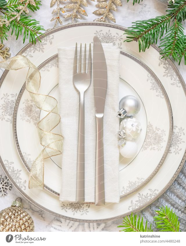 Festive table setting with fir tree branches and Christmas decorations christmas table place ornaments holiday new year marble white golden celebration