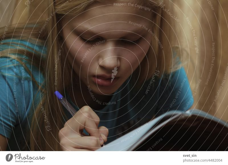 A blonde teenage girl is busy writing in a notebook indoors. write pen concentratedly studying home person caucasian lifestyle homework portrait people sitting