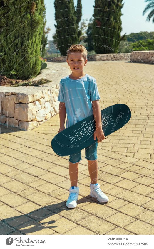 Preschooler boy keep a skateboard in hands in park child sport summer kid family mockup nature lifestyle leisure outdoor t-shirt young skater fun active
