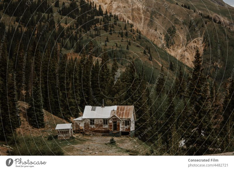Abandoned house in the mountains abandoned house abandoned home Ghost town wrecked and ruined wood home vintage travel adventure trees dark moody mountain range