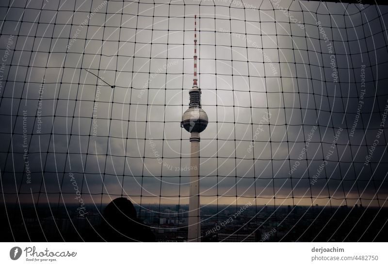 The Berlin TV tower from above, behind a safety net in very bad weather. The horizon can only be seen as a small ray of hope. Tower Landmark Sky Architecture