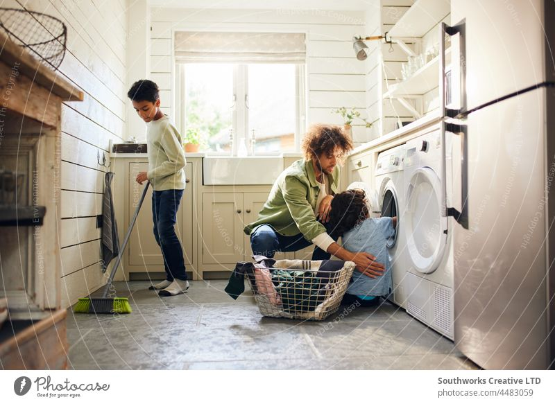 Two boys helping father with household chores mixed race child kitchen sweep broom laundry indoors day home interior three group authentic washing machine