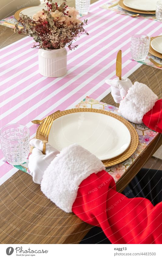 Santa Claus sitting at the table ready to eat arm banquet catering celebrate chairs christmas cutlery december decor design dining elegant empty food fork