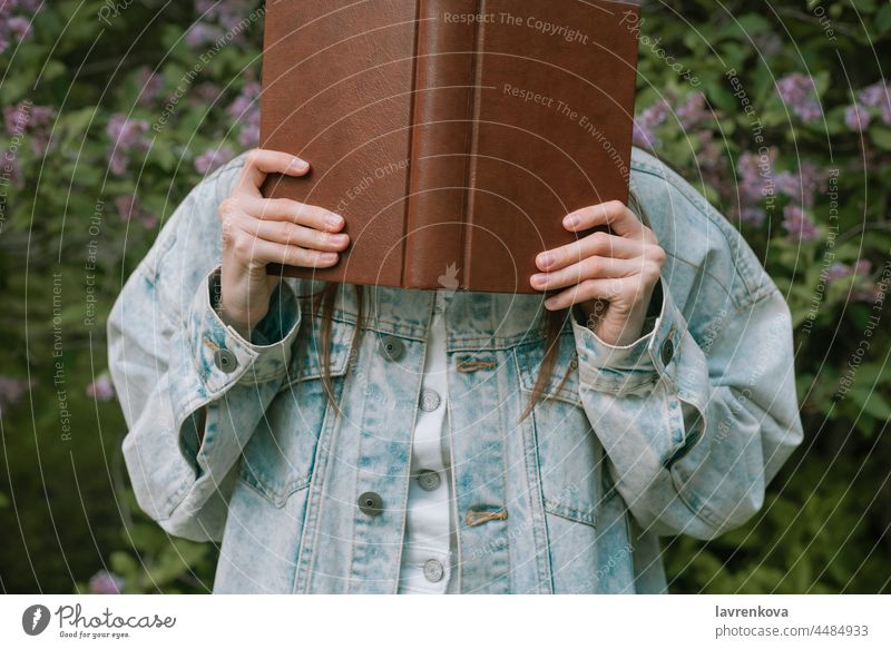 Faceless shot of female holding a book in front of her face outdoors lifestyle young reading portrait education woman intelligent standing green summer hands