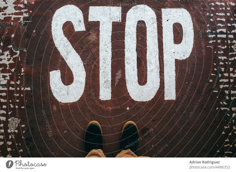 An illegal immigrant stands barefoot at a stop sign on the ground. control entrance entry immigration letters negative personal unrecognizable boundary concrete