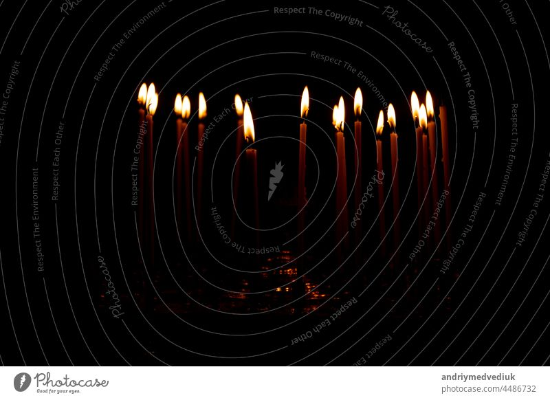 close up a lot of burning candles isolated on black background. candlelight flame fire night glow church religion christmas dark praying glowing religious