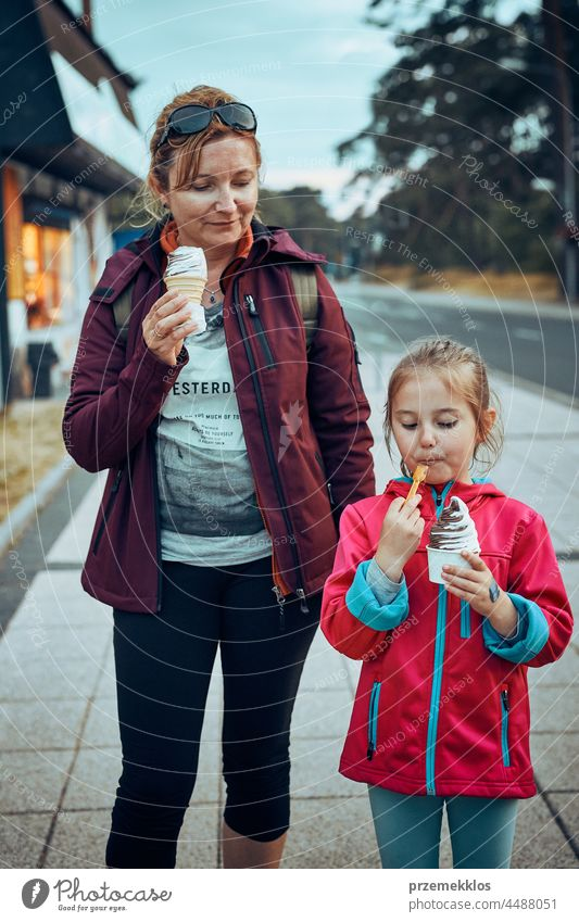 Mother and her daughter enjoying ice cream walking through town afternoon family summer sweet dessert eating person child fun mother happy togetherness parent