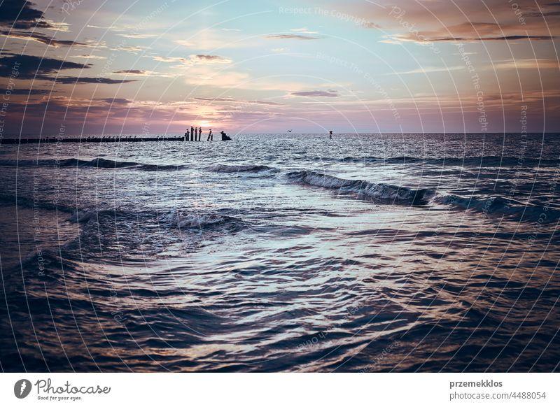 Beautiful sunset over sea horizon. Soft colors, mood and magic, subtle light. Small clouds in the sky seascape landscape dusk twilight beach wave sunlight dawn