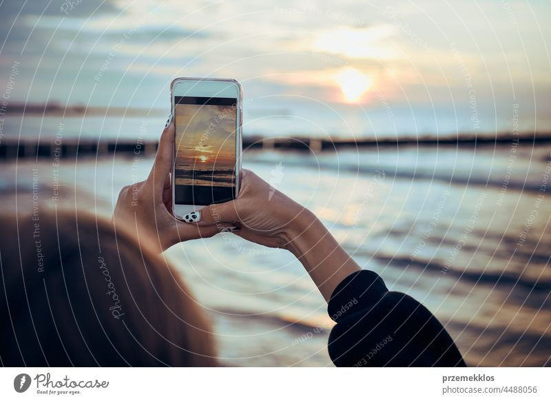 Young woman taking photos of sunset over sea using smartphone during summer trip photographer picture technology screen person female holding ocean photography