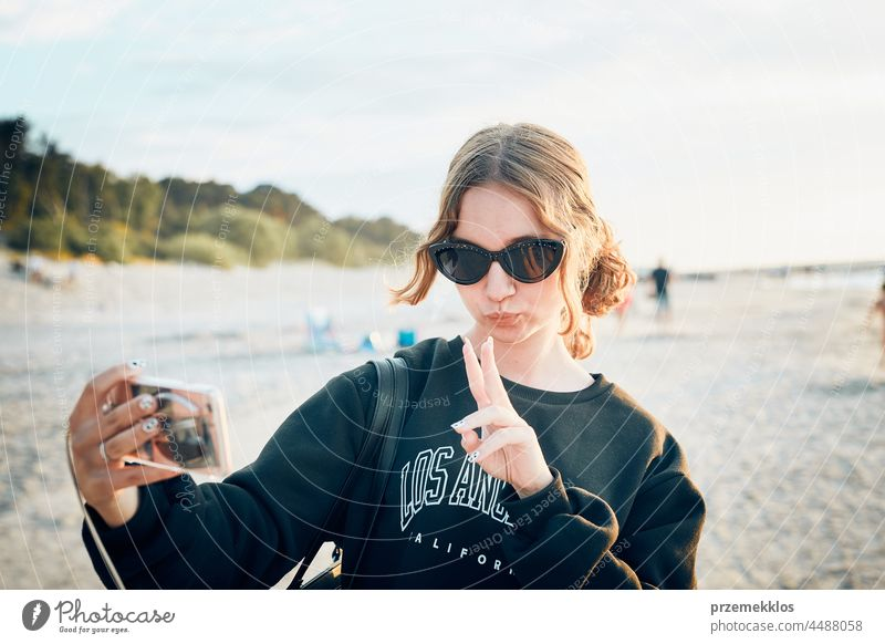 Teenager girl making gesture during video call on smartphone during trip on summer vacation chat greeting taking photo selfie person woman mobile phone holding