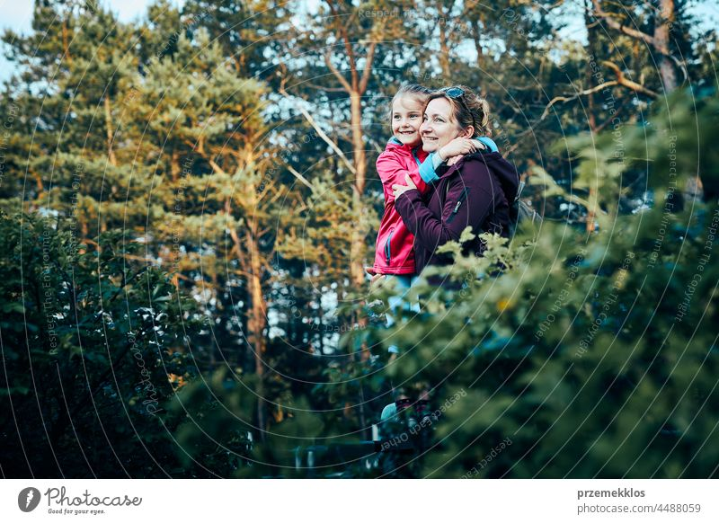 Woman and her dughter admiring landscape actively spending summer vacation together walking down a forest path family outdoor activity nature leisure beauty