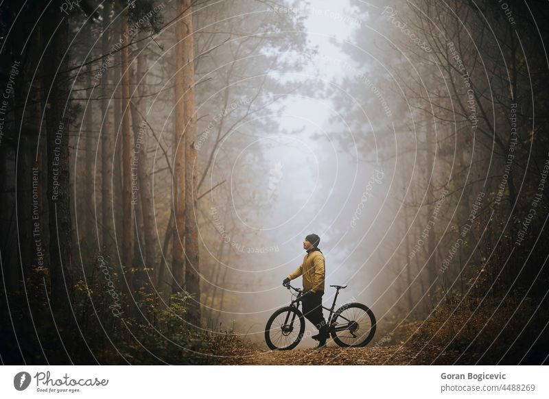 Young man taking a brake during biking through autumn forest action active activity adventure athlete bicycle bicycling bicyclist bike biker exercise extreme
