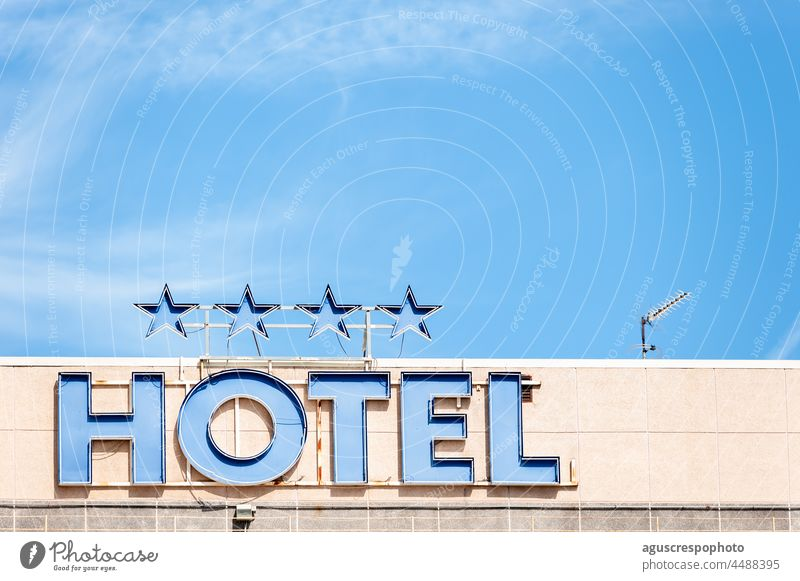"""Top view of a hotel with a sign with the neon lights off that says """"Hotel"""" and 4 stars above built tour tourism holiday facades business architecture metallic"""