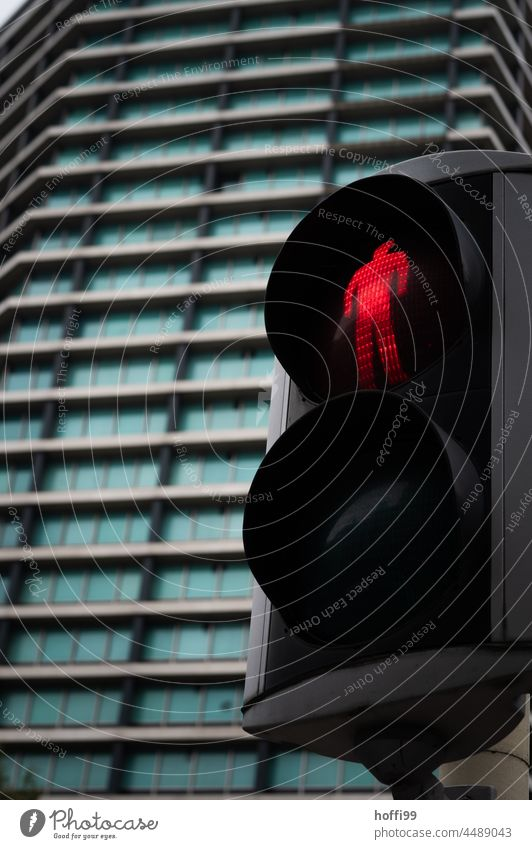red traffic light for pedestrians in front of a high-rise building Red Traffic light ampelmännchen Pedestrian Road traffic Illuminate Pedestrian traffic light