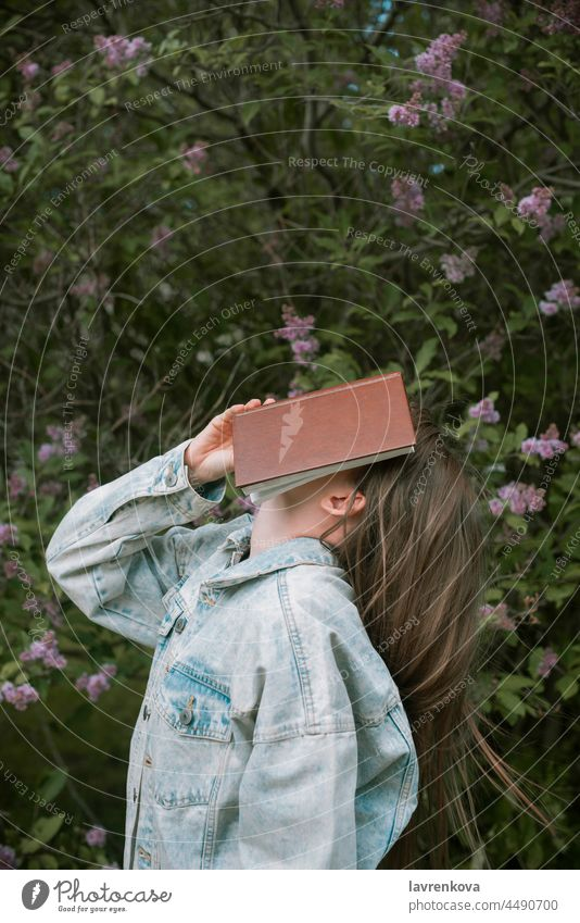 Faceless shot of female holding a book in front of her face outdoors, lifestyle young reading portrait education woman intelligent standing green summer hands