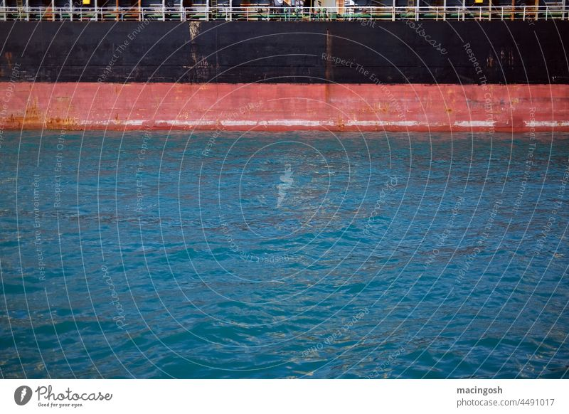 Ship's wall and water surface in the harbour Black Red Blue ship cargo ship Harbour Mooring place Drop anchor Unload loading Navigation logistics