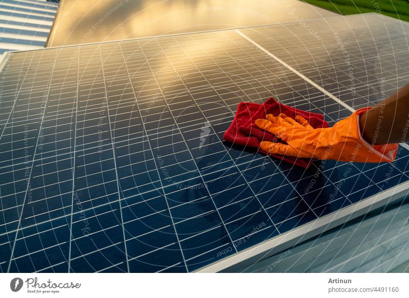 Man cleaning solar panel on roof. Solar panel or photovoltaic module maintenance. Sustainable resource and renewable energy for go green concept.  Solar power for green energy. Technology for future.