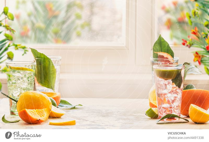 Iced citrus drinks with mint, orange and grapefruit on kitchen table at window with natural light. Homemade healthy lemonade with fruits in summer. Drink background with copy space. Front view.