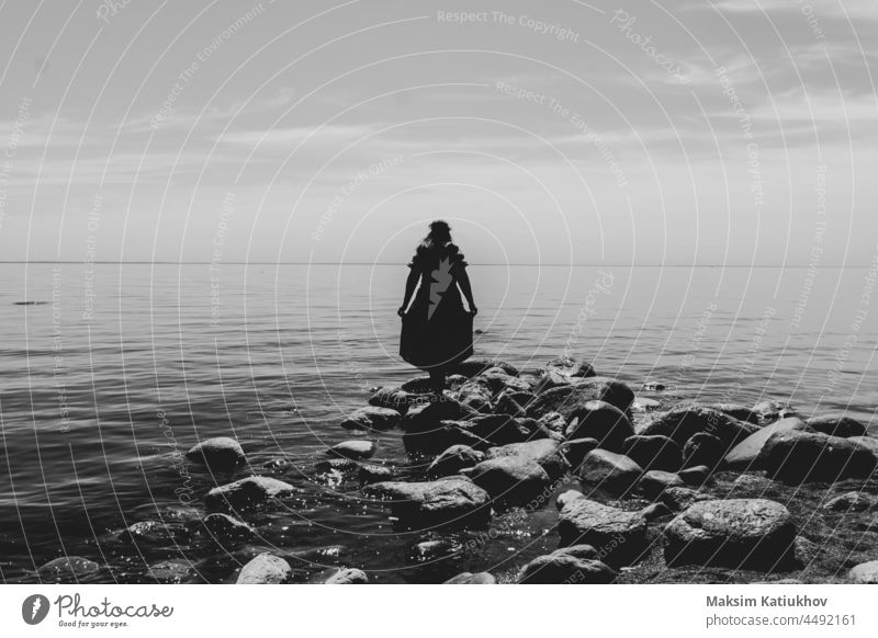 Silhouette of a woman standing on stones at the beach. beautiful summer landscape with horizon line silhouette sand sea people coast water sky shoreline