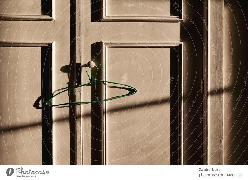 Doors of a wardrobe with green hanger in side light with shadow cast Hanger hangers Cupboard cupboard door Power up Profile strips Closet Wire hangers Sidelight