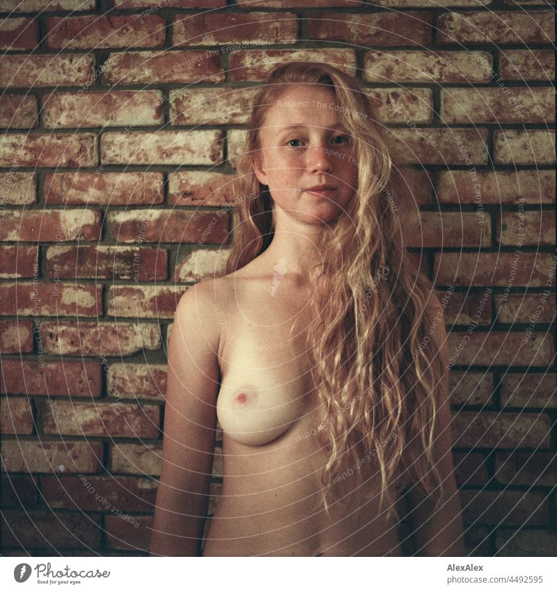 analogue nude portrait of a young woman with freckles and red hair standing in front of a brick wall Emanation tranquillity vigorous pretty Youth (Young adults)