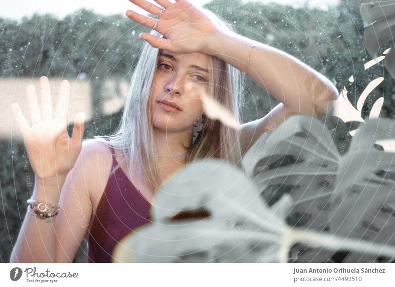 An attractive young woman looking at the camera through glass and surrounded by plants girl pretty lifestyle people garden person white blond hair beauty female