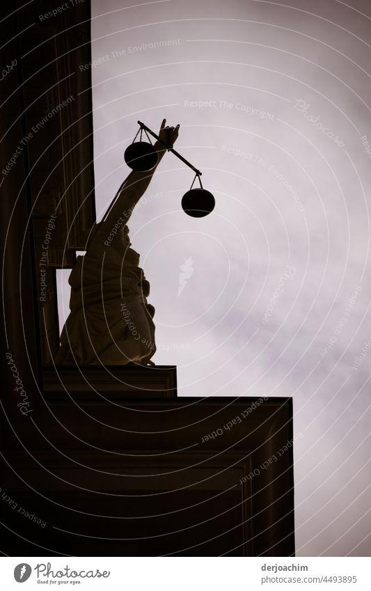 Justicia hält mit ausgestreckter Hand, die Gerechtigkeits Waage. Statue auf dem Humboldt Forum. Der Himmel ist verdunkelt. Berlin. Architecture Modern Facade