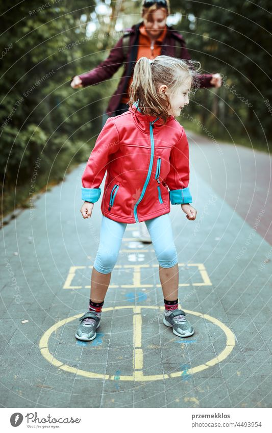 Active little girl playing hopscotch on playground outdoors jumping preschool game child fun chalk outside exercise joy kid active happy sidewalk enjoyment