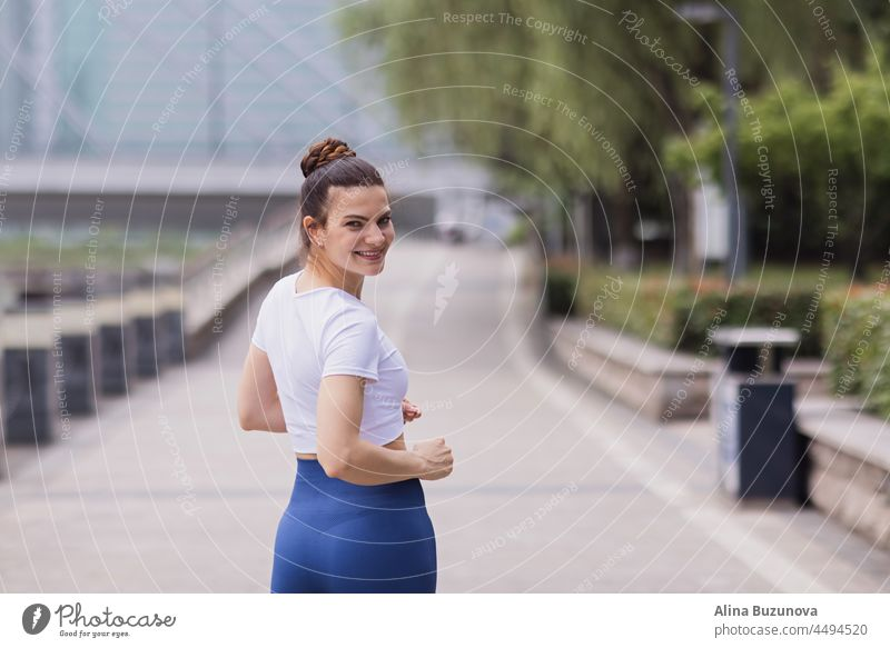 Young brunette Woman running on asphalt road in summer park. Active sporty caucasian female has morning workout. Athletic person in sportswear exercises outdoor. Dressed leggings and sportive top