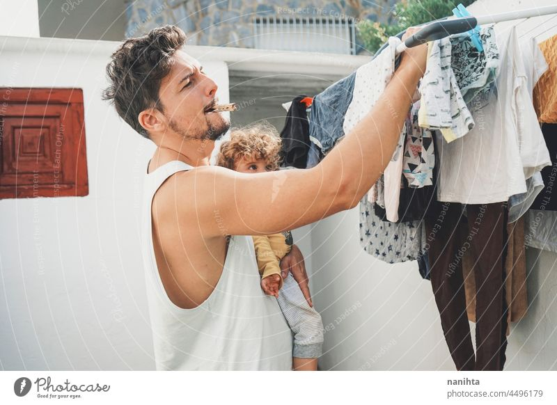 Young man doing the laundry at home clothes wash clean fresh doing laundry backyarkd family baby male modern masculinity youth parent outdoors aire warm dryed