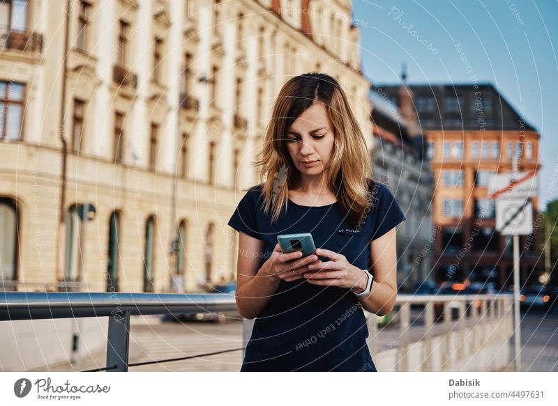 Woman using smartphone at city street Smartphone Mobile Walking Street Lifestyle Communicate Online Portrait Phone Using Happiness Portable Information Device
