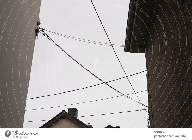 Connections data and power lines between houses from the frog's perspective Cables Data stream Sky Worm's-eye view nobody Gray Electricity Power transmission
