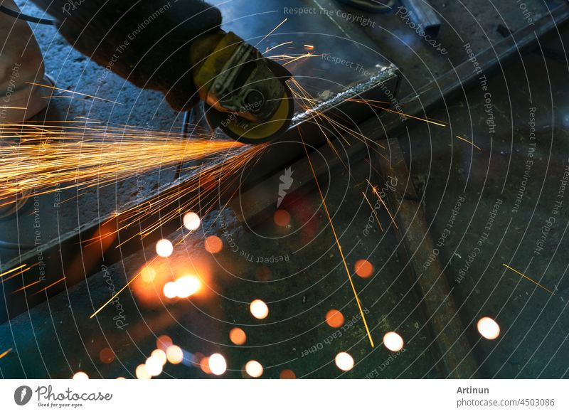 Industrial worker using angle grinder grinding metal on welding seams. Worker working with angle grinder and has sparks. Tool for cut steel. Safety in industrial workplace. Metal factory industry.