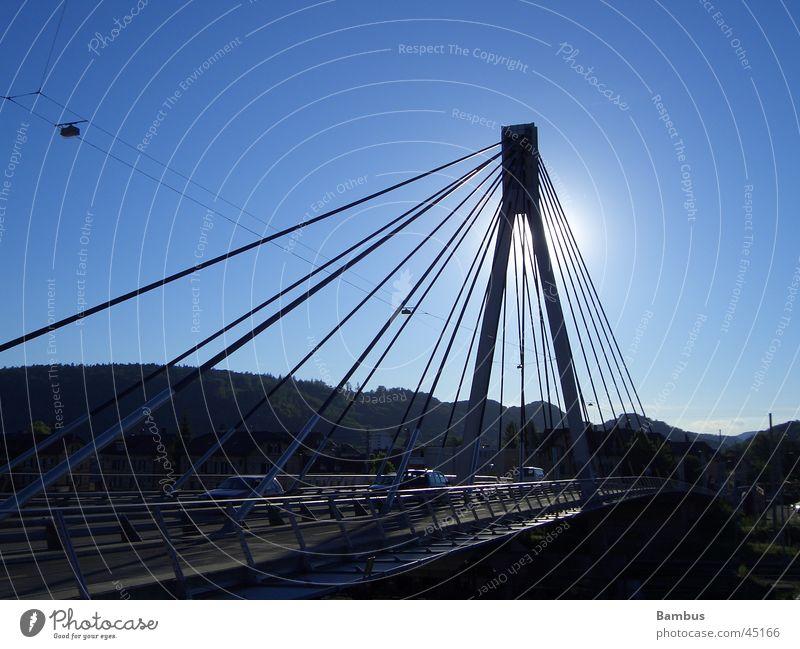Steel beams in backlighting Steel carrier Suspension bridge Back-light Bridge Blue sky Street Sun