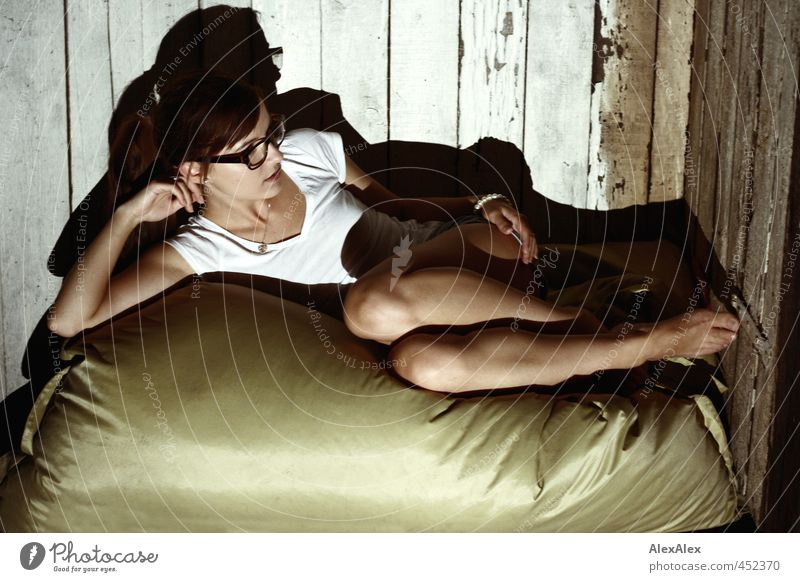 Young, barefoot woman lies on cushions in front of a board wall Attic beanbag Young woman Youth (Young adults) Arm Legs Feet Knee décolleté 18 - 30 years Adults
