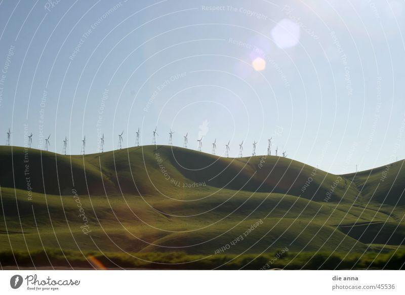 landscape with windmills Meadow Hill Green Grass Mountain Wind energy plant Sun Blue sky Nature