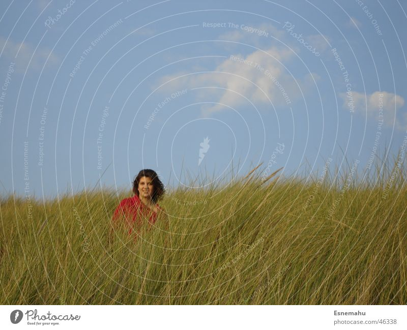 With your back to the sea Clouds Grass Woman Red Green Brown Loneliness Sweater Sky Meadow Blue Human being Wind Hair and hairstyles Colour Clouds in the sky