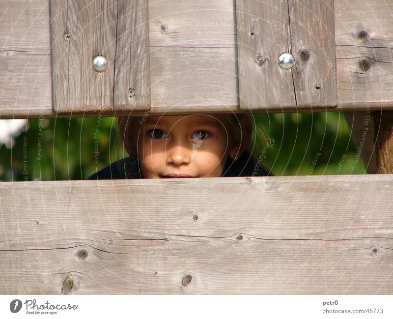 Child Girl Face Eyes Wood Wooden board Playground Hiding place