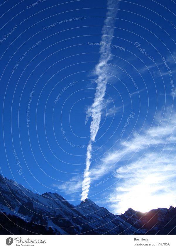 Early evening atmosphere in the Swiss Alps Vapor trail Clouds Mountain Sun Evening Snow Sky Blue