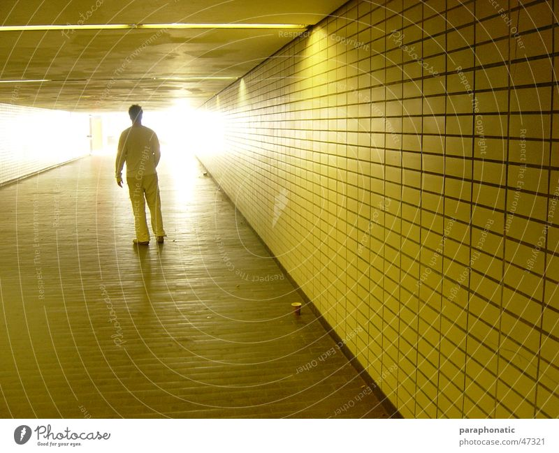 Light in the station Man Multiple Yellow Back-light Lighting Illuminate Shadow play Against Coffee mug Cardboard Floor covering Long Underground Station