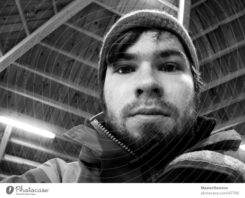 disorientation Portrait photograph Masculine Man Facial hair Lips Beard Cap Woolen hat Jacket Wooden roof Lamp Indifferent Amazed Surprise Unclear Interior shot