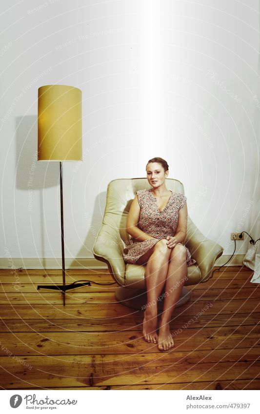 Young barefoot woman in a summer dress sitting in a beige armchair Young woman Youth (Young adults) Legs Feet 18 - 30 years Adults Small room Floorboards