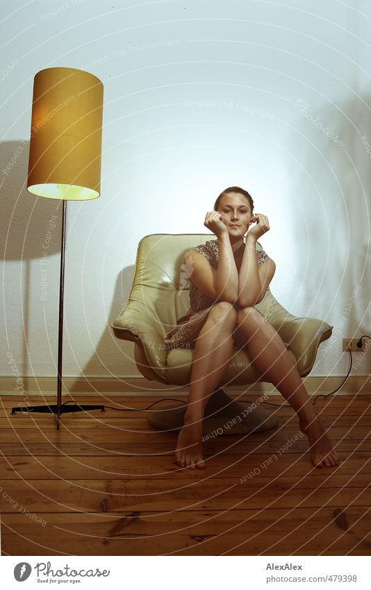 Young woman in dress sitting barefoot on an armchair with her arms to her face Standard lamp Armchair Youth (Young adults) Legs Face Facial expression
