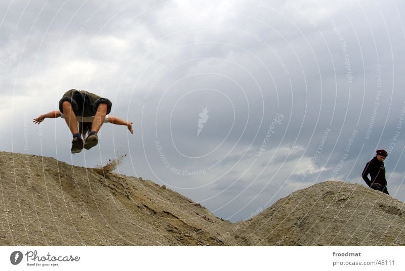 somersault Man Woman Jump Action Gray Bad weather Mining Sand Desert Rain Clouds Flying Movement Dynamics Construction