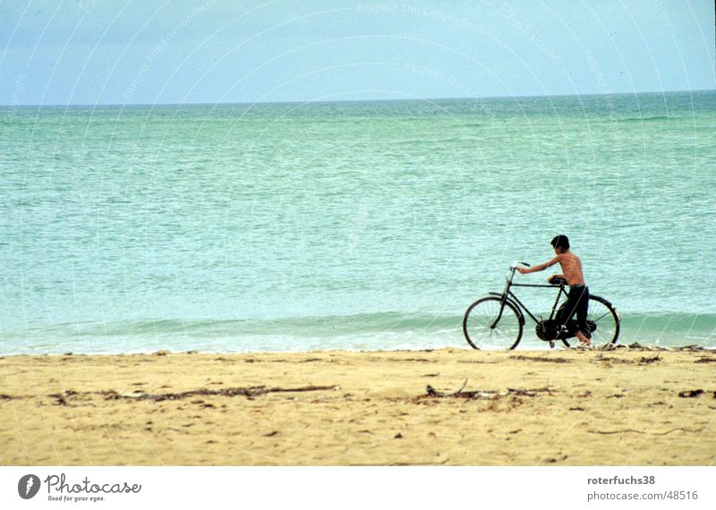 Hainan Dao Haikou China Taoism Coast Beach Child Bicycle Clouds Push Short haircut Asia Surf Calm Hissing Turquoise Ocean Means of transport Yellow Ochre Sky
